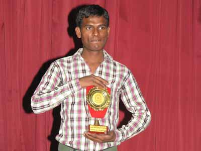 Naushad from Seelampur slum colony holding a trophy he has received from his college for being the highest scorer during the three years of his Bachelors degree in Political Science from Delhi University