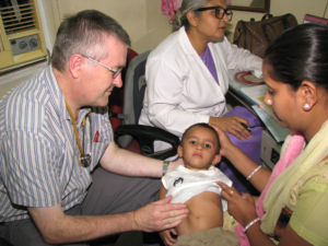 Dr Richard Hogben from the UK examining a child at the Asha Polyclinic