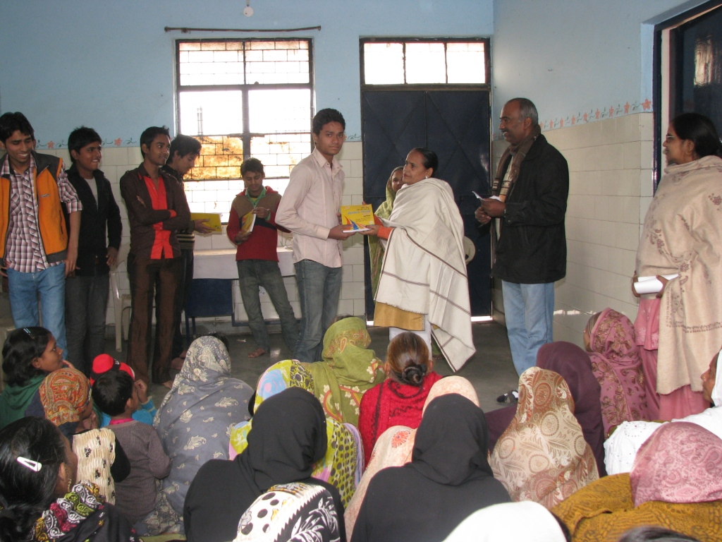 A Class XII student receiving books from Asha in the presence of Women's Group members