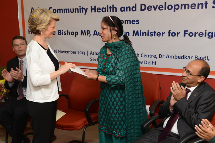 Ms. Bishop presents the cheque to Asha's Programme Manager, Ms. Kiran Gera as HE Suckling and Mr. Varghese look on