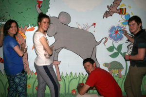 Ballymena Academy team painting the Tigri center in a vibrant jungle theme