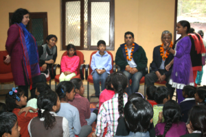 A children's group member shares her story with the guests