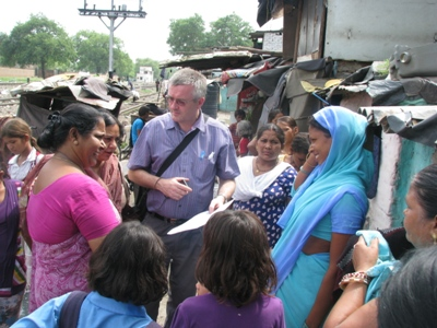 Dr Hogben examines health records of a patient during his visit to Mayapuri slum colony