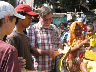 The team observe a child health card during their visit to the slum