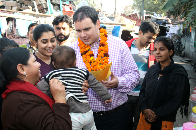 Mr Appleton examines an infant health card during his visit to the slum colony