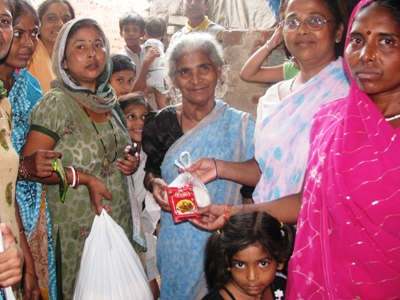 Women's group at an Asha slum provides food supplies to an old lady