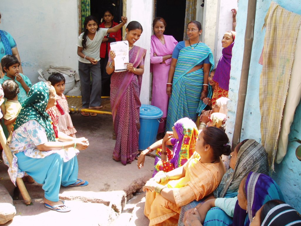 An Asha CHV holding a public meeting with women from the slum to create awareness about reproductive health