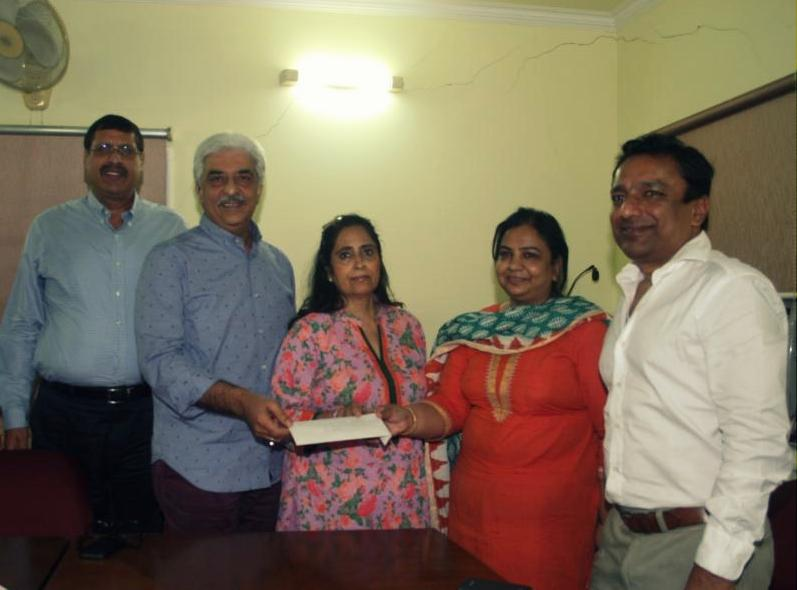 Asha's Senior Programme Coordinator, Ayesha Seymour receives the generous gift from Mrs and Mr Lekhi