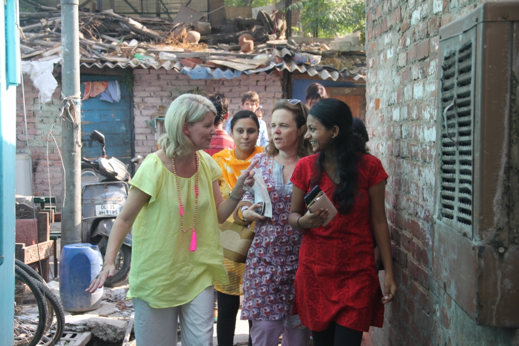 Ms Despoja talks to Babita (in red) on her way to Babita's home in the slum