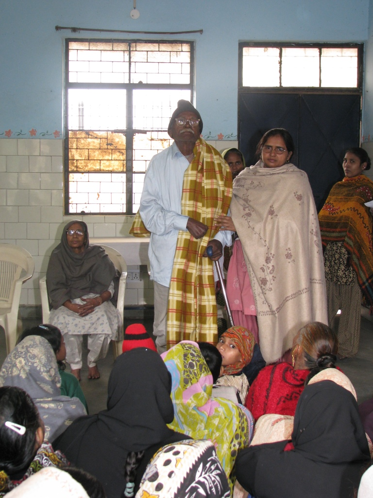 Asha staff presenting a blanket to an elderly person living in Seelampur slum colony