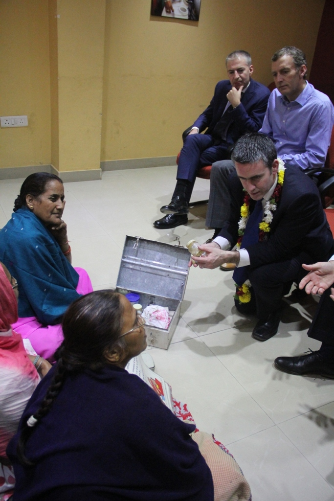 Minister looks at the contents of a Community Health Volunteer's medicine box