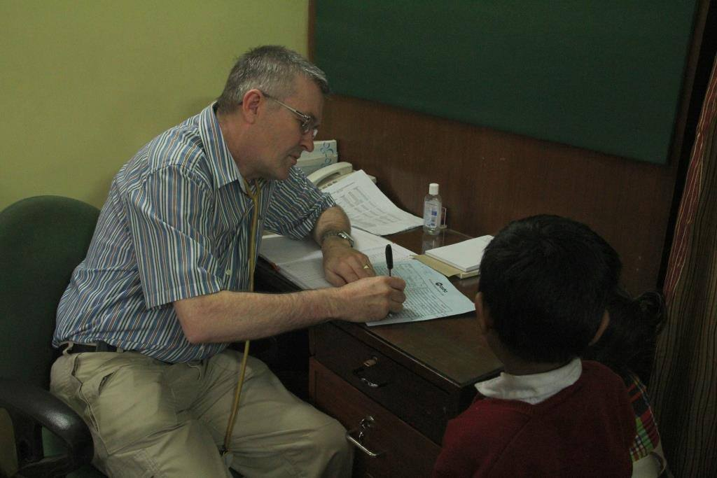 Dr Dick with a patient at Asha polyclinic