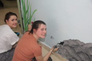 Royal school students painting the walls at Asha 's Trilokpuri slum centre