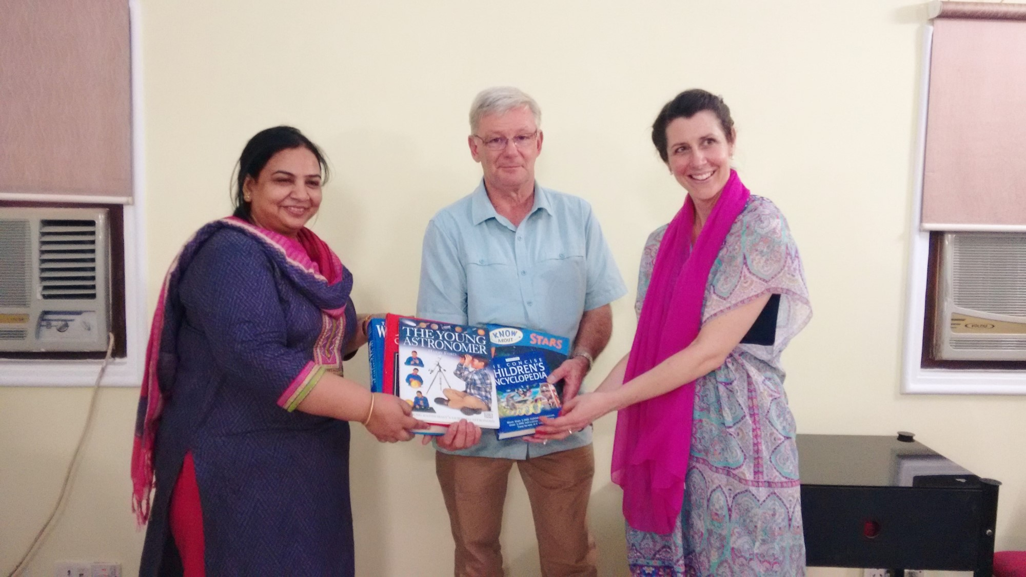 Long time Asha supporter and trustee of Gryphon School, Nigel Rees (center) and teacher Anna-Louise Griffiths (right) presenting books for Asha children