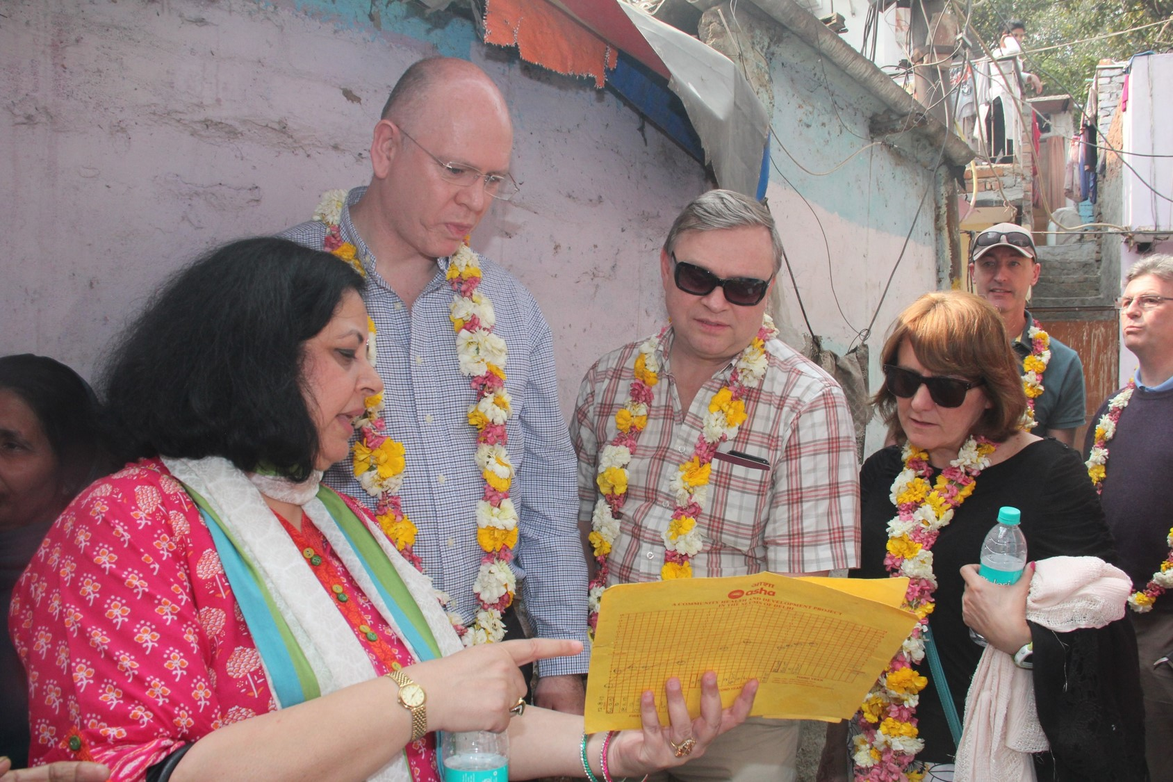 During the slum visit, Dr Kiran explaining about the 'child health cards' maintained by the Asha team.