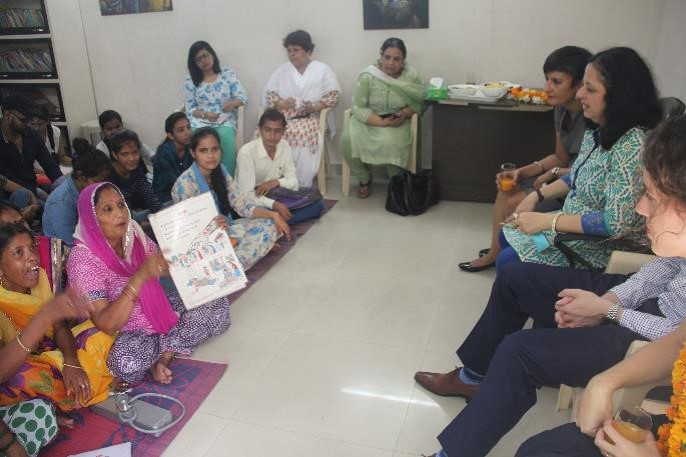 Asha Community Health Volunteer explains the flashcard to Ms Sidhu.