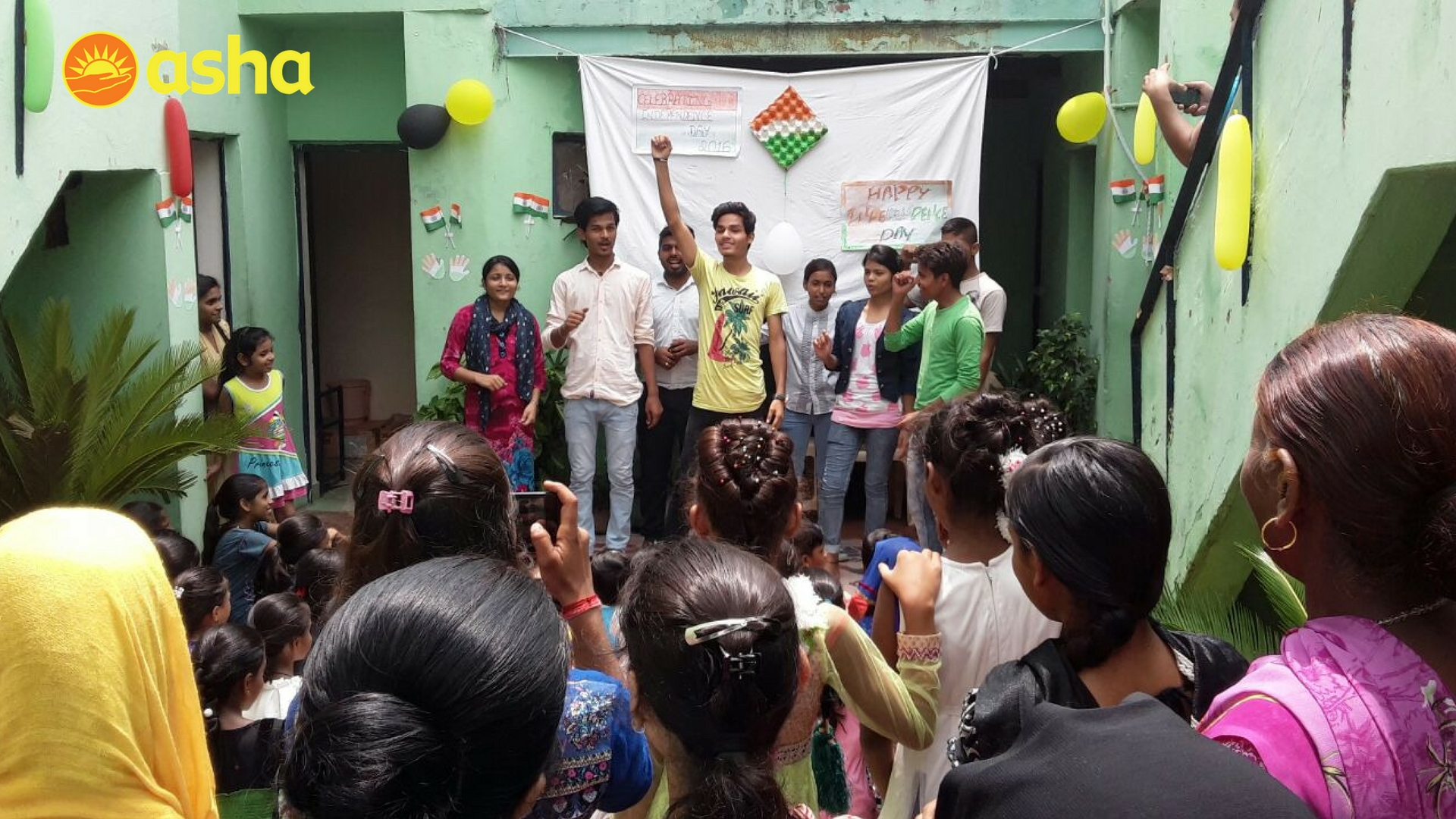 Asha college students enacting a play at Kalkaji centre while the Children and Women's Association cheer for them.