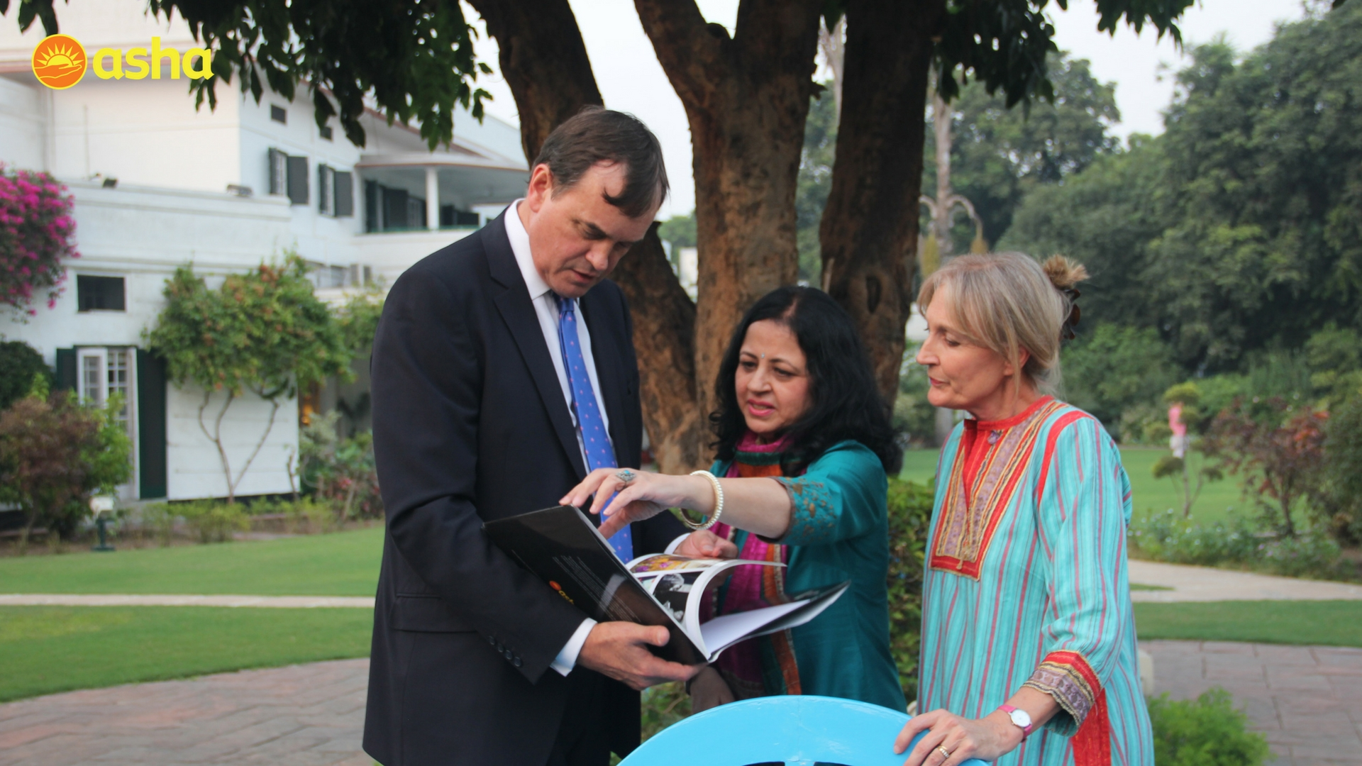 Dr. Kiran showing of Asha's work to the Honourable High Commissioner Sir Dominic Asquith KCMG and his wife, Lady Louise Asquith.