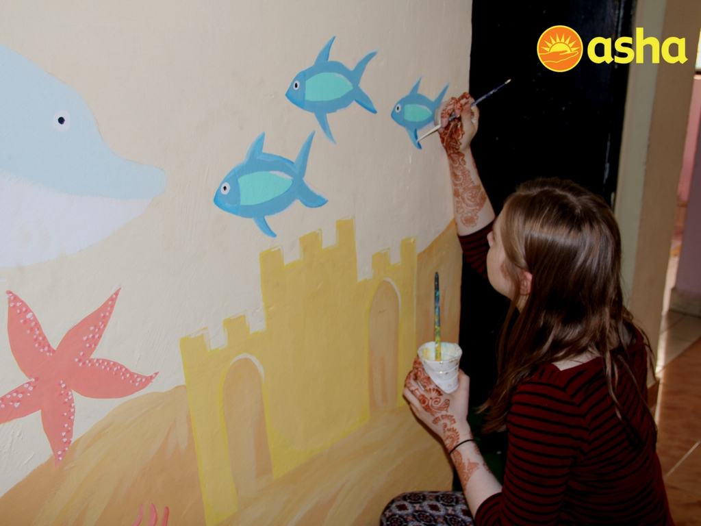 One of the student of Rainey Endowed painting a mural at the Asha centre