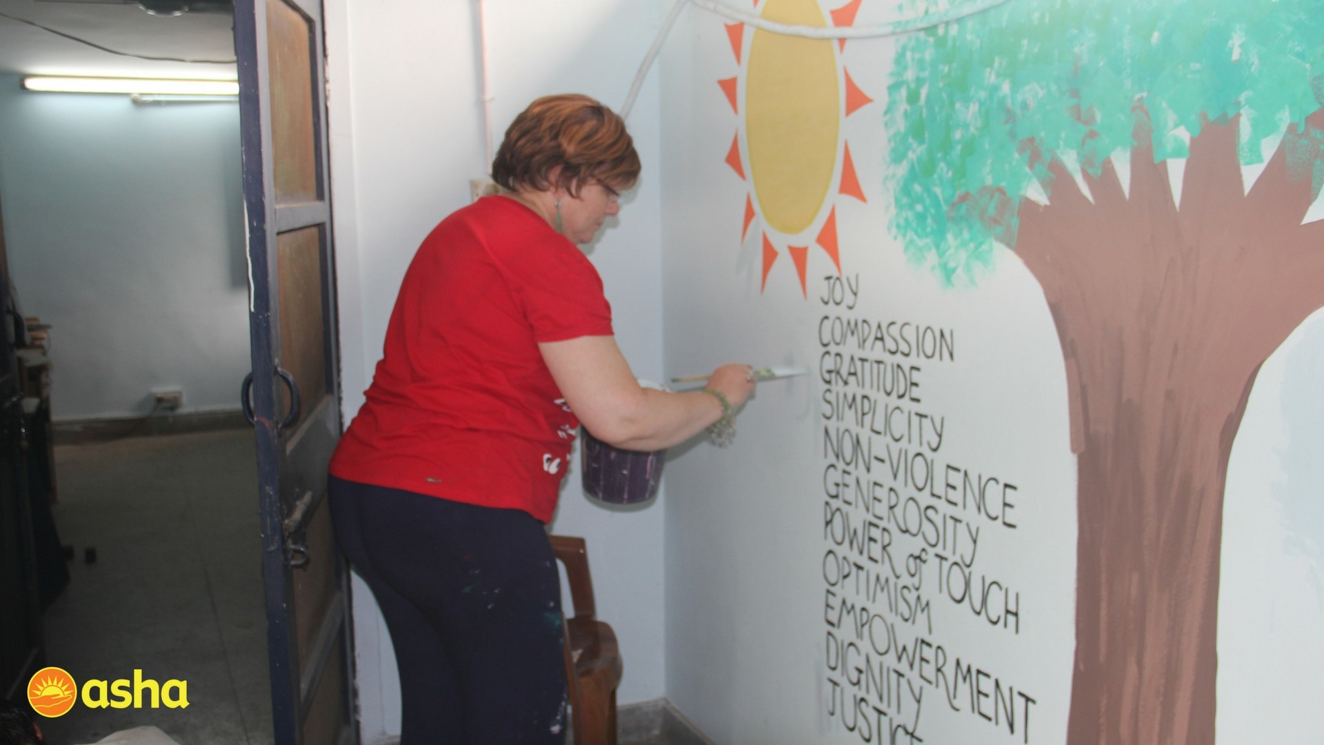 Methodist College's team lead, Ruth McKibben painting the Asha Values.