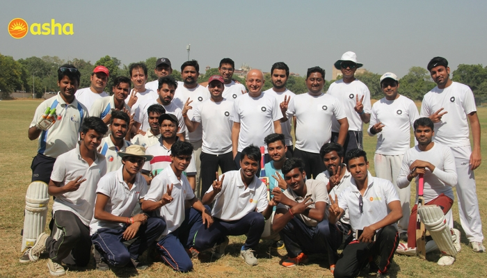 The Macquarie-Asha cricket team happily pose for a group picture.