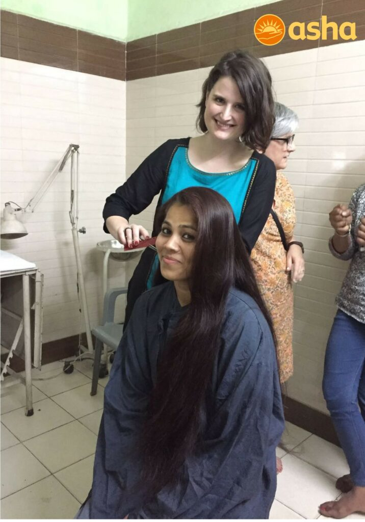 Emily Furste styling a girl's hair at the centre.