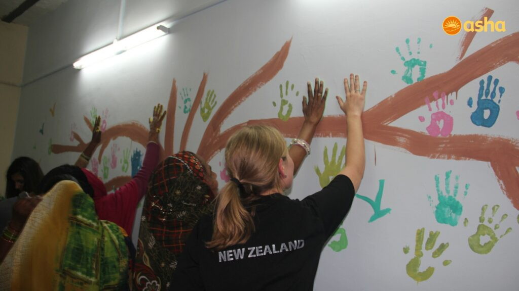 The enthusiastic gathering putting hand impressions on the wall.