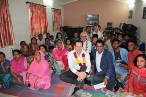 Mathew Canavan and Freddy Martin pose for a group picture with the Asha community