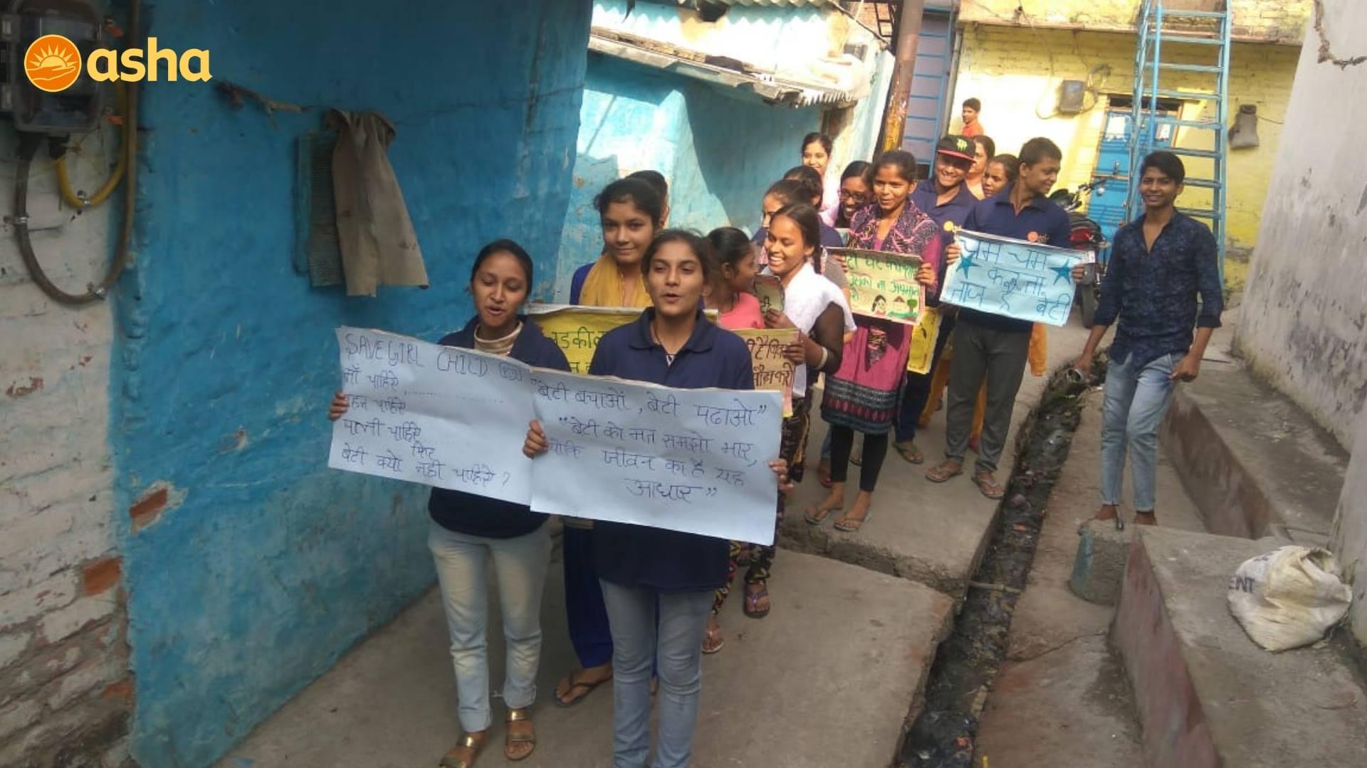 Asha's V. Singh campus's children rallying across the slum