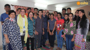 Dr Monica and her parents posing with Asha students and Ms Rani, Asha Supervisor