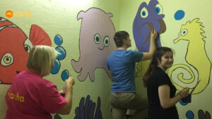 Dunclug team painting the murals on the walls