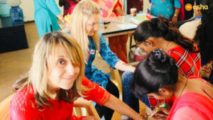 Asha students applying henna on the hands of Wallace team members