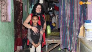 Dr Kiran Martin with a child at Asha's Chanderpuri slum community