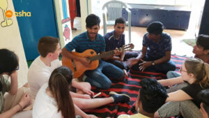 Asha student playing guitar and singing songs with the Dunclug team