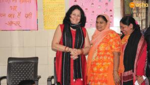 Dr Kiran Martin posing with an Asha's Mahila Mandal member