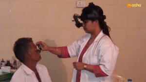 A medical staff examining an elderly patient in Asha's Mayapuri slum community