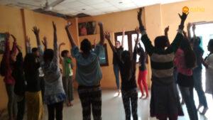 Jessie helping the children perform an activity at Asha's Dr Ambedkar Basti
