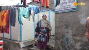 Shabrunisha posing in front of the community toilet she helped to build