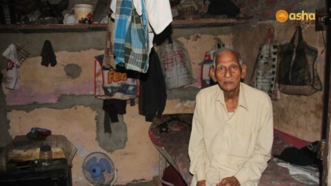 Elderly man living alone in the slums cared for by Asha